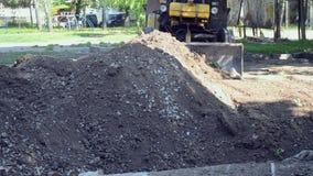 De tractor verwijdert grondvuil, graaft gatenbouwwerf stock videobeelden