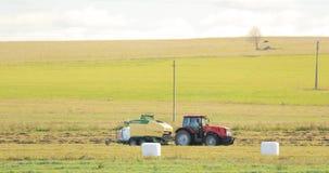 De tractor verzamelt Droog Gras op Straw Bales In Summer Wheat-Gebied Speciale Landbouwmachine Hay Bales, Hay Making stock footage