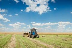 De tractor verzamelt droog hooi op het landbouwbedrijfgebied royalty-vrije stock fotografie
