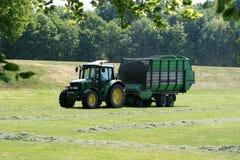 De tractor verzamelt gras Stock Fotografie
