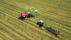 De tractor verzamelt hooi van de gebiedsmening van de hommel stock afbeelding