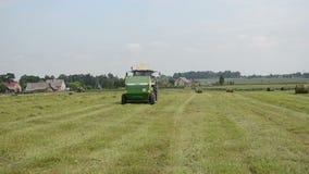 De tractor verzamelt hooigebied stock video