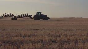 De tractorbewegingen over het gebied, die de grond na oogstlandbouw ploegen stock video