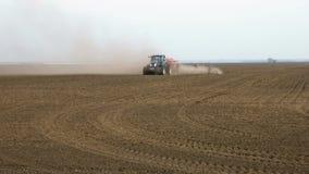 De tractorploegen bewerkt ploegen en zaden op het gebied stock videobeelden
