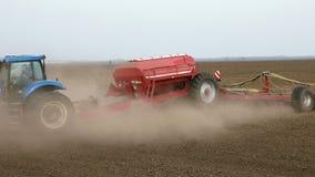 De tractorploegen bewerkt ploegen en zaden op het gebied stock video