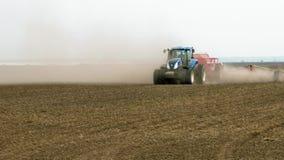 De tractorploegen bewerkt ploegen en zaden op het gebied stock footage