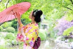 De traditionele Aziatische Japanse mooie Geishavrouw draagt kimonobruid met een rode paraplu in a graden stock foto's