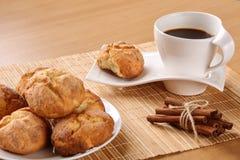 De traditionele Bulgaarse koekjes, genoemd kurabiiki, kop van koffie en gebonden pijpjes kaneel op een beige bamboe dienen mat in Stock Foto's