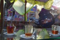 De traditionele die thee van een theepot wordt gegoten vormt in Arabische Koffie tot een kom stock foto