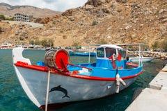 De traditionele Griekse die vissersboot blijft bij haven van de stad van Chora wordt vastgelegd Sfakion royalty-vrije stock afbeelding