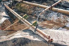 De traditionele Japanse plechtige die bamboegietlepels worden gebruikt aan waren handen alvorens de tempel in te gaan stock afbeeldingen