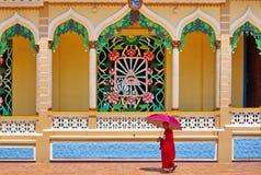 De traditionele kleurrijke tempel en de monnik van Cao Dai met umbrellain Vietnam Stock Foto's