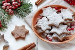 De traditionele koekjes van de Kerstmispeperkoek, sterren in gepoederde suiker op de plaat Bessen van de rode sparren van de Lijs Stock Afbeeldingen