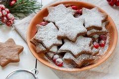 De traditionele koekjes van de Kerstmispeperkoek, sterren in gepoederde suiker op de plaat Bessen van de rode sparren van de Lijs Royalty-vrije Stock Afbeelding