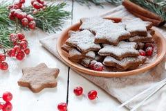 De traditionele koekjes van de Kerstmispeperkoek, sterren in gepoederde suiker op de plaat Bessen van de rode sparren van de Lijs Stock Foto