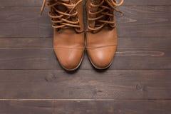 De traditionele laarzen van de leercowboy zijn op de houten achtergrond Stock Foto