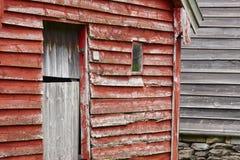 De traditionele Noorse houten rode gekleurde cabine huisvest voorgevels O Stock Foto's