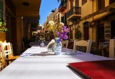 De traditionele reeks van Griekenland - het witte tafelkleed van straattavernas op de lijst aangaande de achtergrond van oude str stock fotografie