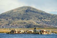 De traditionele rietboot en de huizen op Meer Titicaca, een groot, diep meer in de Andes op de grens van Bolivië en Peru, vaak ca stock fotografie