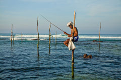 De traditionele visser van Srilankan op stok in de Indische Oceaan Stock Afbeelding
