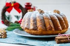 De traditionele vruchtencake voor Kerstmis verfraaide met gepoederde suiker en noten, rozijnen en kop van koffie of thee stock foto
