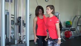 De trainer controleert de cliënt in de gymnastiek De vrouw slingert handen stock video