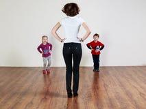De trainer en twee kinderen doen oefeningen royalty-vrije stock afbeeldingen