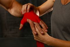 De trainer helpt bokser om polsen met rode omslagen te verpakken royalty-vrije stock foto