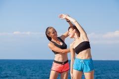 De trainer helpt het meisje om de oefeningen te doen royalty-vrije stock afbeelding