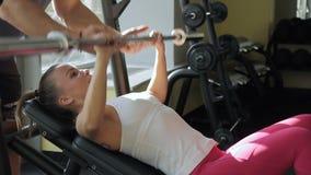 De trainer helpt sportvrouw om de pers van de hellingsbarbeel in de moredngymnastiek te doen stock video