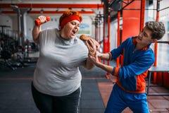 De trainer neemt hotdog bij vette vrouw, motivatie stock foto's