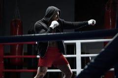 De training van de boksermens in boksring In dozen doende vechter in hoodie Royalty-vrije Stock Afbeelding