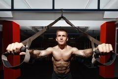 De training van de geschiktheidsmens op de ringen in de gymnastiek Stock Foto