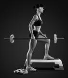 De training van de geschiktheidsvrouw met barbell bij gymnastiek stock afbeelding