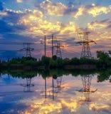 De transmissietoren van de silhouetmacht tijdens schemeringtijd stock foto