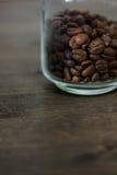 De transparante die kruik van de glaskoffie met bonen van koffie over de donkere houten lijst wordt gevuld Stock Foto's