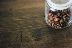De transparante die kruik van de glaskoffie met bonen van koffie over de donkere houten lijst wordt gevuld Royalty-vrije Stock Fotografie