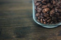 De transparante die kruik van de glaskoffie met bonen van koffie over de donkere houten lijst wordt gevuld Stock Afbeelding