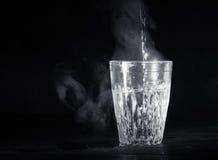 De transparante glaskop met zwelt het kokende water in het De damp vanaf de bovenkant Zwarte achtergrond royalty-vrije stock afbeelding