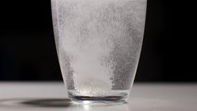 De transparante glaskop van water laat vallen analgin tablet stock footage