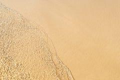 De transparante golf is inherent op een zandig strand Royalty-vrije Stock Fotografie