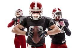 De tre amerikanska fotbollsspelarna som poserar med bollen på vit bakgrund Arkivbild