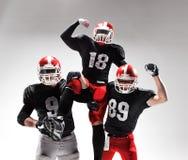 De tre amerikanska fotbollsspelarna som poserar på vit bakgrund Royaltyfri Foto