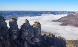De tre systrarna ovanför dimma på de blåa bergen Australien royaltyfri fotografi
