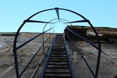 De treden van de metaalbrandtrap met ronde veiligheidstunnel gelegen aan de bouw van muur royalty-vrije stock fotografie