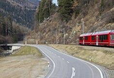 De Trein en de weg van alpen Stock Afbeelding