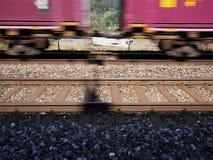 De trein gaat met snelheid voor een snelweg over Stock Foto's