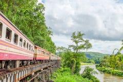 De trein loopt op de sporen, is de spoorweg Thailand-Birma bij de Wereldoorlog II de spoorwegen werd gebouwd door de klip naast Stock Foto