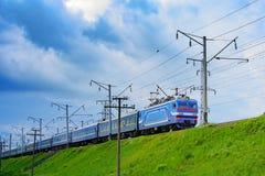 De trein reist naar een vergadering van de streek met grijze wolken stock fotografie