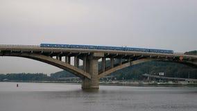 De trein reist over de brug tegen de hemel en de bos buiten verlaten Stadsmetro Openbaar vervoer in beweging De vector van auto's stock video